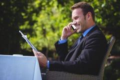 Hübscher Geschäftsmann auf dem Telefon und dem Ablesen des Menüs Stockfotos
