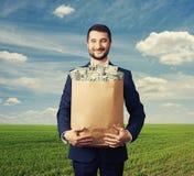 Hübscher Geschäftsmann, der Papiertüte mit Geld hält Stockfoto