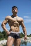 Hübscher, heißer junger Bodybuilder hemdlos in den Stämmen Lizenzfreies Stockbild