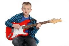 Hübscher Junge, der auf roter E-Gitarre spielt Stockfoto