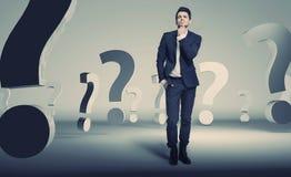 Hübscher junger Geschäftsmann über Frage Stockfotografie