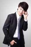 Hübscher junger Geschäftsmann, der Handy verwendet Stockbild