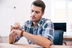 Hübscher junger Mann, der auf Armbanduhr schaut Stockbilder