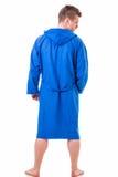 Hübscher junger Mann, der den blauen Bademantel, lokalisiert trägt Stockfotos