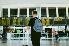 Hübscher junger Mann, der in den Flughafen geht Stockfotografie
