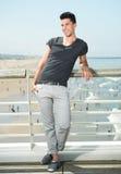 Hübscher junger Mann, der an der Küste lächelt Stockbilder