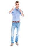 Hübscher junger Mann, der sich Daumen zeigt Stockfotos