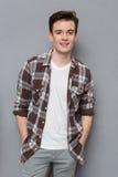 Hübscher junger Mann im karierten aufwerfenden und lächelnden Hemd Stockfotos