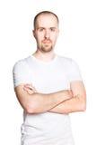 Hübscher junger Mann mit den gefalteten Armen im weißen T-Shirt Stockfoto