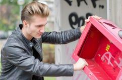 Hübscher junger männlicher Vandale, der Öffentlichkeit bricht Lizenzfreies Stockbild