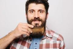Hübscher kaukasischer Mann mit lustigem Schnurrbartlächeln und kämmen seinen großen Bart Stockfoto