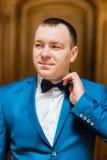 Hübscher lächelnder Mann in blauem Anzug fixin seine Fliege im reichen hölzernen Innenraum Stockbild