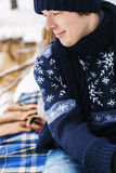 Hübscher lächelnder Mann, der im Winterwald auf Plaid sitzt Stockfotos