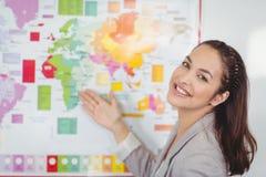 Hübscher Lehrer, der Weltkarte in einem Klassenzimmer zeigt Stockbilder