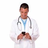 Hübscher männlicher Doktor, der eine Mitteilung simst Stockfotos