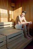 Hübscher, muskulöser, junger Mann, der in einem alleindenken der Sauna sitzt Stockbilder