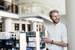Hübscher Student, der in der Bibliothek lächelt Lizenzfreie Stockbilder