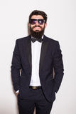 Hübscher tragender Anzug und Gläser des jungen Mannes, die Hände in den Taschen halten und Kamera betrachten Lizenzfreie Stockfotografie