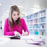 Hübscher, weiblicher Kursteilnehmer mit Laptop und Bücher Stockfotografie