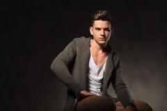 Hübscher zufälliger Mann, der auf dunklem Studiohintergrund sitzt Stockbilder