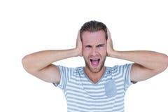 Hübscher zufälliger Mann, der mit der Hand auf Ohren schreit Stockfoto