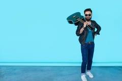 Hübscher zufälliger Mann in der schwarzen Lederjacke mit Gitarre Stockbild