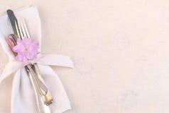 Hübsches Gedeck mit Gabel, Messer, Löffel, Kirschblüte auf Sahnetischdecke Stockfotos