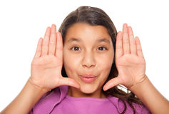 Hübsches hispanisches Mädchen, das ihr Gesicht mit den Händen gestaltet Stockfoto