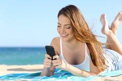 Hübsches Jugendlichmädchen, das ein intelligentes Telefon liegt auf dem Strand verwendet Stockbilder