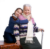 Hübsches Mädchen, das auf einem Kasten sitzt und ihre Großmutter umarmt Stockfotografie