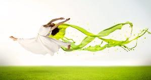 Hübsches Mädchen, das mit grünem abstraktem flüssigem Kleid springt Stockfoto