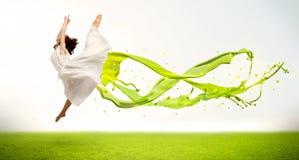 Hübsches Mädchen, das mit grünem abstraktem flüssigem Kleid springt Lizenzfreie Stockfotografie