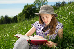 Hübsches Mädchen mit Daisy Flower In Her Mouth, die interessantes Buch im Gras lesend genießt Stockfoto