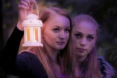Hübsches Mädchen zwei in der Dunkelheit mit einer Lampe Lizenzfreie Stockfotos