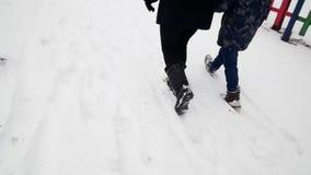 HD关闭妇女和孩子的脚射击走开在深雪的冬天公园的 股票视频