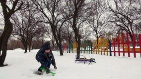 HD快乐的男孩充当与儿童` s铁锹的雪 股票录像
