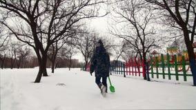 HD快乐的男孩在与儿童` s铁锹的雪走开 股票视频
