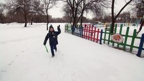 HD快乐的男孩是跑和挥动与儿童在雪的` s铁锹 股票录像