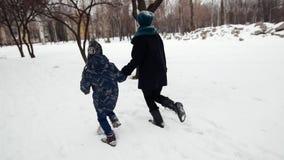 HD母亲和儿子在深雪的冬天公园愉快地跑 股票录像