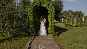HD πυροβοληθε'ν το κινηματογράφηση σε πρώτο πλάνο γαμήλιο ζεύγος αγκαλιάζει και φιλά στο πράσινο τόξο στο πάρκο απόθεμα βίντεο