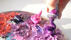 HD Συμπιέσεις καλλιτεχνών από το σωλήνα στο πορφυρό ελαιούχο χρώμα παλετών στοκ εικόνες