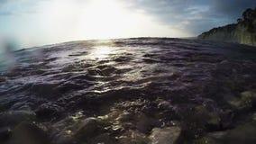 波浪滚动在与太阳强光的日落在岩石的岩石海滨 股票视频
