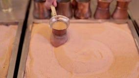 Человек делает турецкий кофе на горячем песке, близком взгляде Турецкий кофе будучи завариванным неопознанным человеком на горяче сток-видео