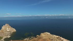Aerial view of Shamanka Rock, Olkhon Island, Baikal lake. Scenic unique rock cliff edge, orange mountain, shamanic. HD aerial shot of Shamanka Rock, Baikal lake stock video footage