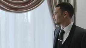 HD-brudgummen står bredvid fönster för ceremoni stock video