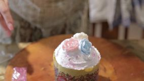 Confectioner woman and girl prepare Easter cakes and decorate them with colorful decor, woman prepares cakes in her own stock footage