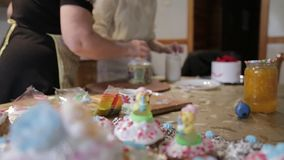 Confectioner woman and girl prepare Easter cakes and decorate them with colorful decor, woman prepares cakes in her own stock video footage