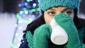 HD de dichte omhoog geschotene Kerstmistijd een meisje is koelend en drinkend thee naast Kerstboom stock videobeelden