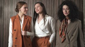 Three beautiful young girls in business suits. Business style. stock video
