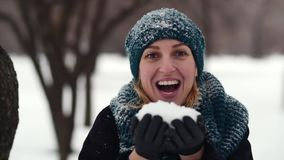 HD Happy young woman holds full plams of snow and blow it out